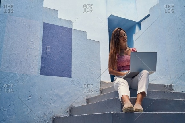 Beautiful woman sitting in blue staircase in a blue building on the computer