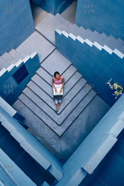 Top view of beautiful woman sitting in blue staircase in a blue building on the computer looking at camera