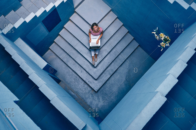 Top view of beautiful woman sitting in blue staircase in a blue building on the computer