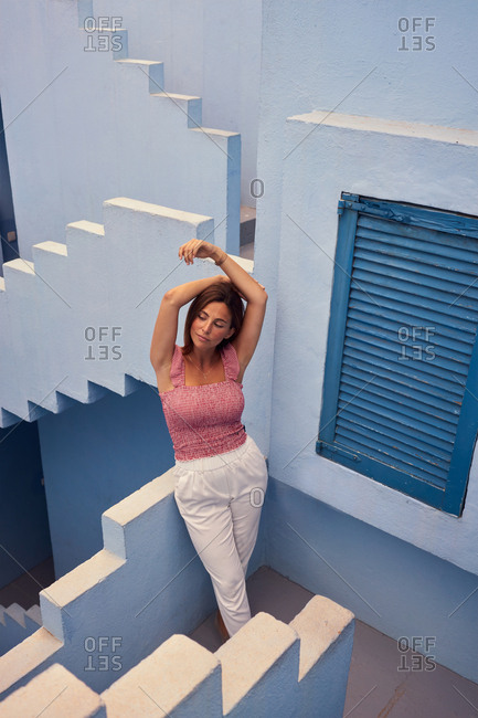 From above top view of young woman walking upstairs on modern blue building closed eyes