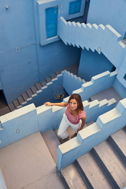 From above top view of young woman walking upstairs on modern blue building looking at camera