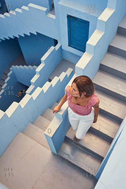 From above top view of young woman walking upstairs on modern blue building looking away