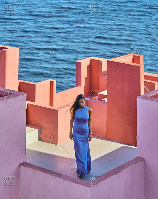 From above of woman in blue fur dress on the roof of a building