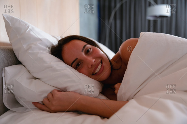 Portrait close up of a young Caucasian brunette woman lying on her side in bed smiling to camera
