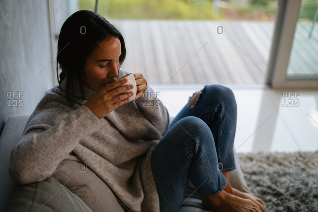 Elevated view of a young Caucasian brunette woman sitting on a sofa with her legs drawn up enjoying a cup of coffee