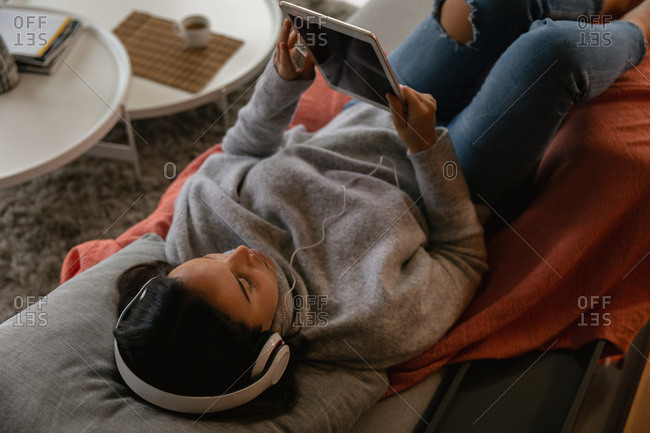 Elevated view of a young Caucasian brunette woman lying on her back on a sofa wearing headphones and watching a tablet computer