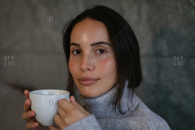 Portrait close up of a young Caucasian brunette woman looking to camera smiling and holding a cup of coffee