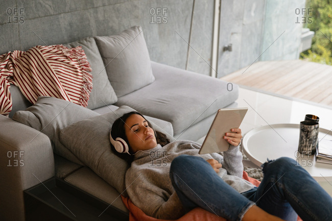 Elevated view of a young Caucasian brunette woman reclining on a sofa with her legs up, wearing headphones and watching a tablet computer