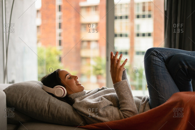 Side view of a smiling young Caucasian brunette woman reclining on a sofa with her legs up, wearing headphones and holding a smartphone