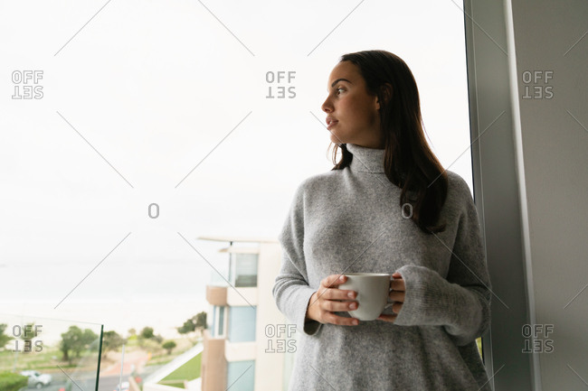 Front view of a young Caucasian brunette woman wearing a grey turtleneck sweater, standing on a balcony holding a cup of coffee with her head turned to the side, looking away