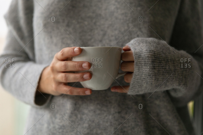 Front view mid section of a young Caucasian brunette woman wearing a grey sweater holding a cup of coffee
