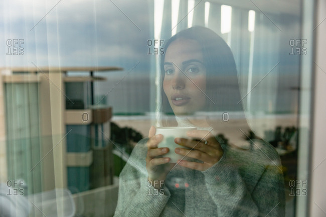 Front view close up of a young Caucasian brunette woman wearing a grey sweater, standing and looking out of a window, holding a cup of coffee, seen through the window with reflections of the buildings outside
