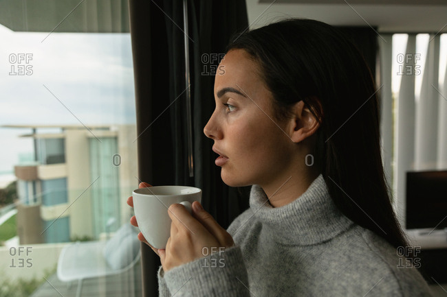 Side view close up of a young Caucasian brunette woman wearing a grey turtleneck sweater, looking out of a window holding a cup of coffee, buildings visible in the background