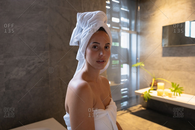 Portrait of a young Caucasian brunette woman wearing a bath towel and with her hair wrapped in a towel, looking straight to camera in a modern bathroom
