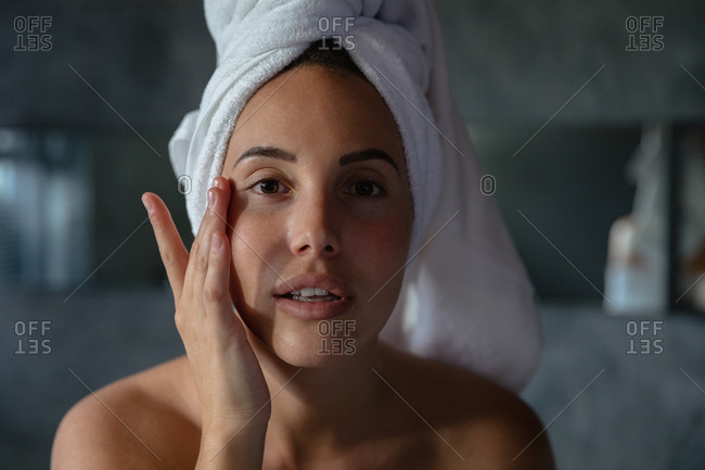 Portrait close up of a young Caucasian brunette woman with her hair wrapped in a towel, looking straight to camera and touching her face with one hand in a modern bathroom