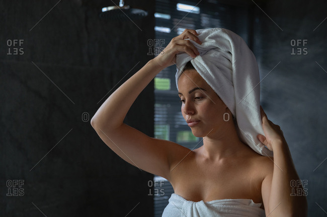 Front view close up of a young Caucasian brunette woman wearing a bath towel wrapping her hair in a towel, in a modern bathroom