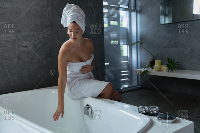 Front view of a young Caucasian woman wearing a bath towel and with her hair wrapped in a towel, sitting on the edge of the bath and touching the water in a modern bathroom