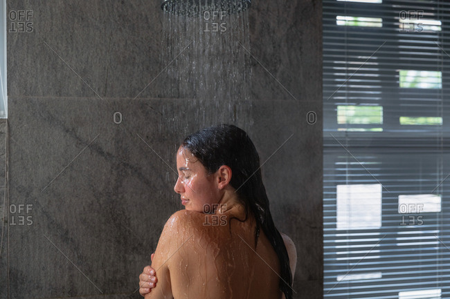 Rear view of a young Caucasian brunette woman standing under the shower washing her hair, with her head turned to the side in a modern bathroom