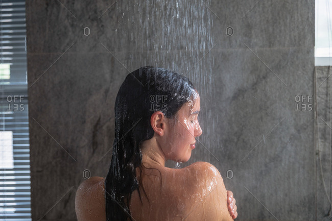 Close up rear view of a young Caucasian brunette woman standing in a shower washing her hair, with her head turned to the side in a modern bathroom