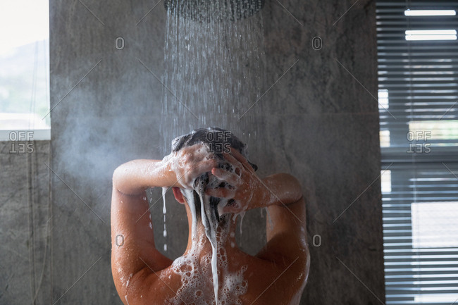 Close up rear view of a young Caucasian brunette woman standing under the shower shampooing her hair in a modern bathroom