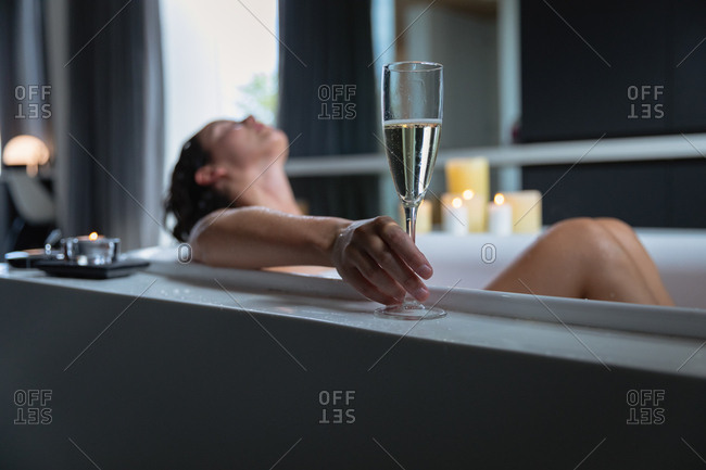Side view of a young Caucasian brunette woman lying in a bath with a lit candles on the side, leaning back and holding a glass of champagne