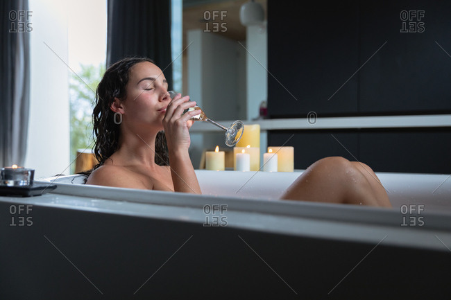 Side view of a young Caucasian brunette woman sitting in a bath with lit candles on the side, drinking champagne with her eyes closed