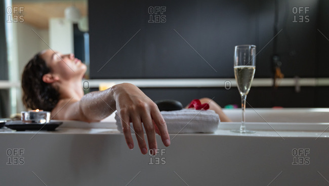 Side view of a young Caucasian brunette woman lying in a bath with a lit candle and a glass of champagne on the side, leaning back with her eyes closed