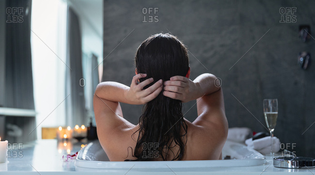 Rear view of a young Caucasian brunette woman sitting in a bath with lit candles and a glass of champagne on the side, adjusting her hair