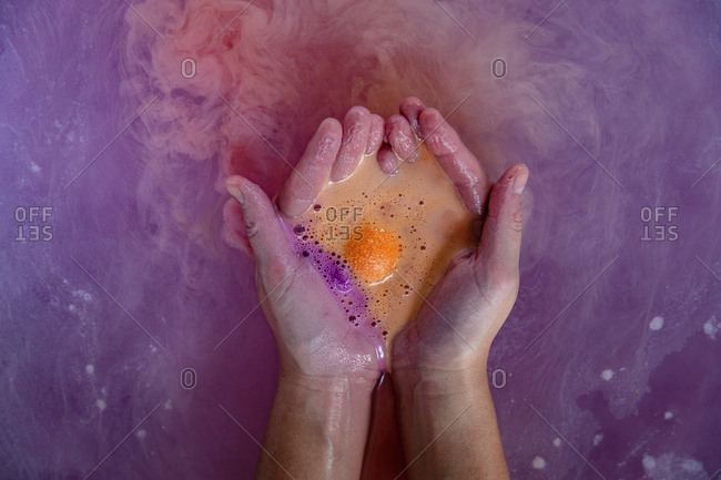 Close up of the cupped hands of a young Caucasian woman in a bath holding effervescing orange bath salts in the pink bath water