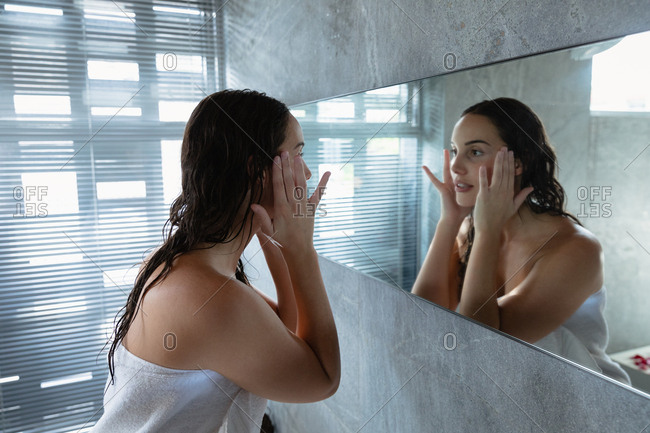 Side view close up of a young Caucasian brunette woman wearing a bath towel looking in the mirror and massaging her face with her fingers in a modern bathroom