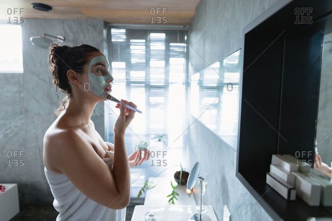 Side view of a young Caucasian brunette woman wearing a bath towel looking in the mirror holding a jar and applying a face pack to her face with a brush in a modern bathroom