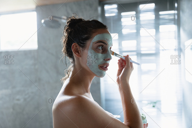 Side view close up of a young Caucasian brunette woman wearing a bath towel looking in the mirror and applying a face pack with a brush in a modern bathroom