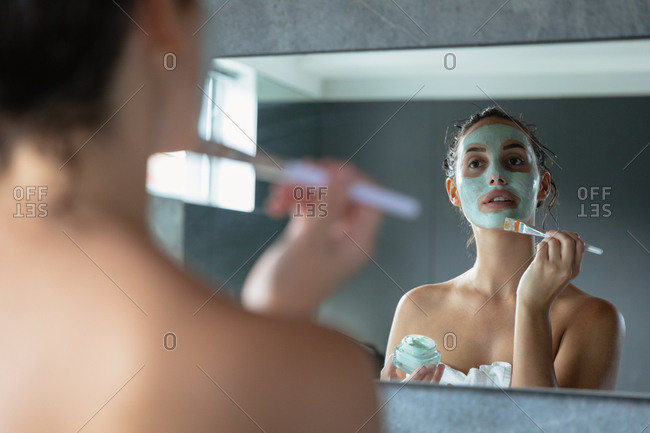 Over the shoulder view of a young Caucasian brunette woman wearing a bath towel looking in the mirror holding a jar and applying a face pack with a brush in a modern bathroom