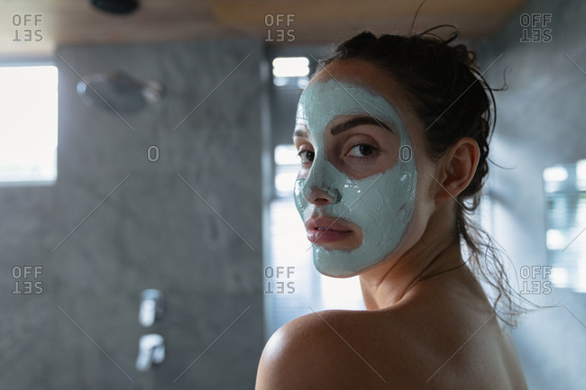 Side view close up of a young Caucasian brunette woman wearing a face pack turning around to look to camera in a modern bathroom