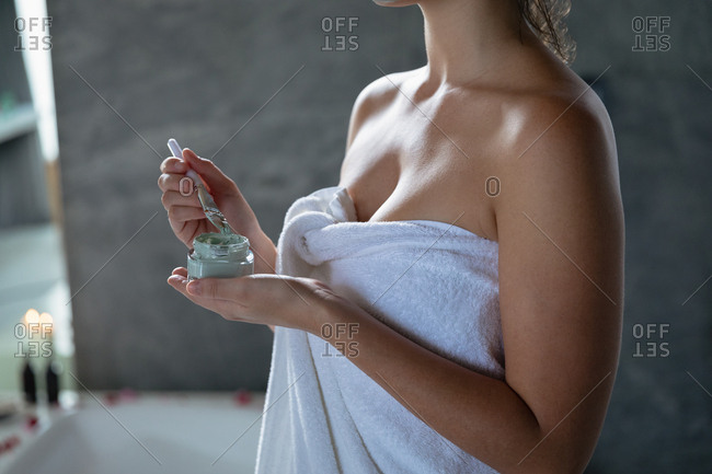 Mid section of a young Caucasian woman wearing a bath towel holding a jar of face pack and dipping in a satchel in preparation to apply it to her face