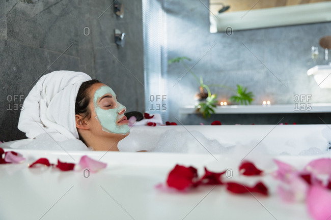 Side view of a young Caucasian brunette woman lying in a bath with lit candles and rose petals on the side, leaning back with her hair wrapped in a towel and her eyes closed