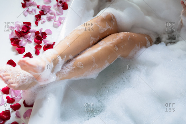 Close up the legs of a young Caucasian woman, raised up on the edge with rose petals on the side, while she lies in a foam bath
