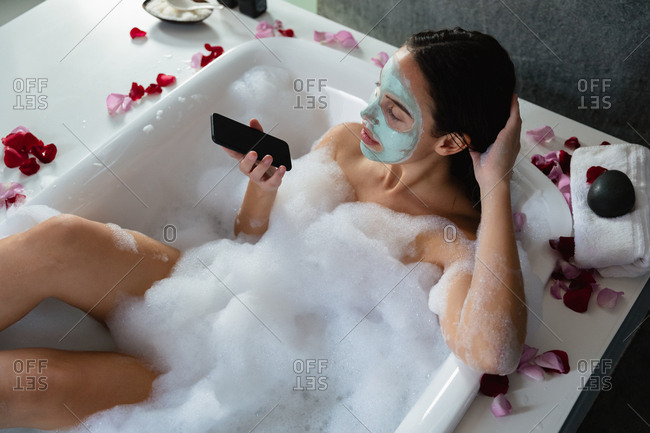 Elevated view of a young Caucasian woman wearing a face pack, sitting in a foam bath with rose petals around the edge using a smartphone