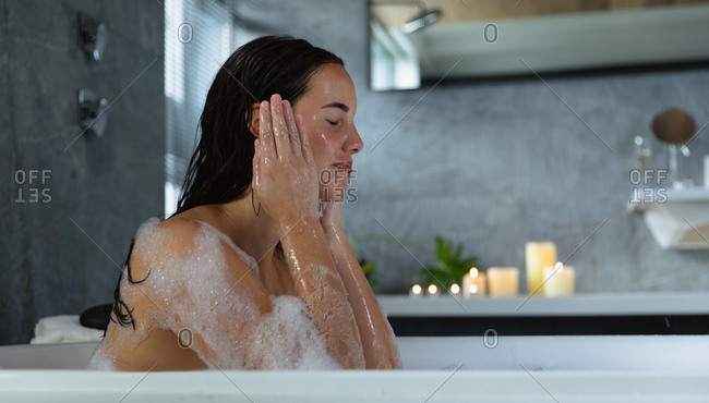 Side view close up of a young Caucasian brunette woman sitting in a bath with lit candles on the side, washing her face with her eyes closed
