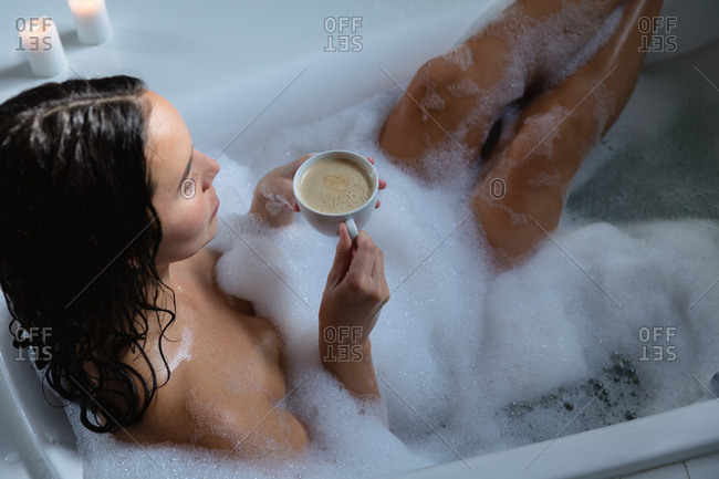Elevated view of a young Caucasian brunette woman sitting in a foam bath with her feet up holding a cup of coffee