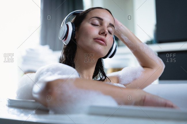 Front view close up of a young Caucasian brunette woman sitting in a foam bath wearing headphones, listening to music with her eyes closed