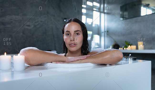 Portrait of a young Caucasian brunette woman sitting in a foam bath with lit candles on the edge, leaning on the side and looking straight to camera