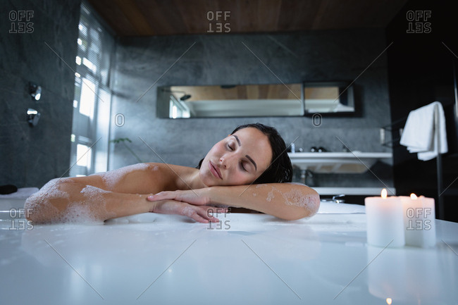 Portrait of a young Caucasian brunette woman sitting in a foam bath with lit candles on the edge, leaning on the side and resting with her eyes closed