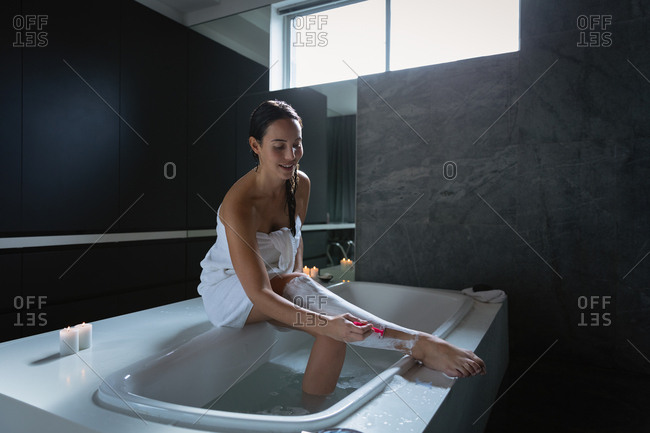 Side view of a young Caucasian brunette woman sitting on the side of a bath shaving her legs