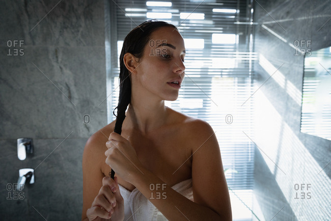Front view close up of a young Caucasian brunette woman conditioning her hair and tunings her head away from camera, standing in a modern bathroom with light streaming in through a window blind behind her