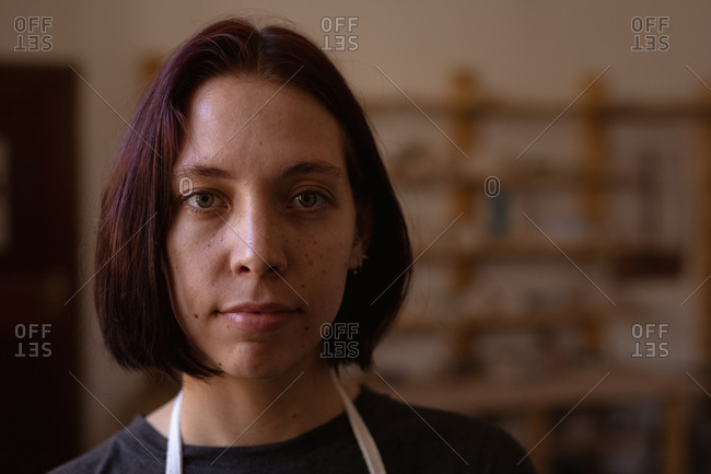 Portrait close up of a young Caucasian female potter looking straight to camera in a pottery studio