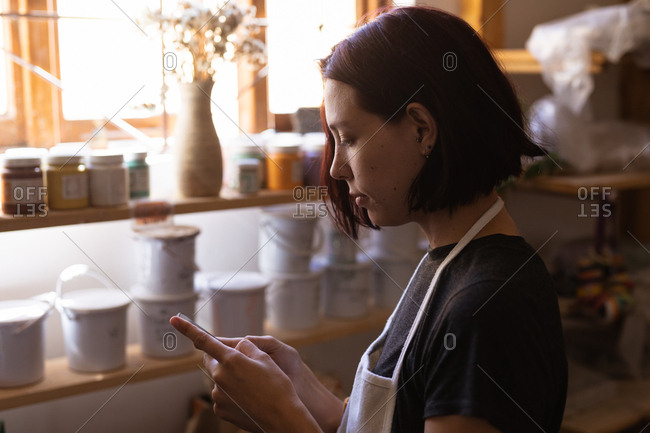 Side view close up of a young Caucasian female potter using a smartphone in a pottery studio