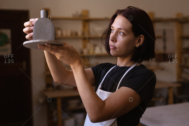 Side view close up of a young Caucasian female potter holding a clay flask and looking at it in a pottery studio