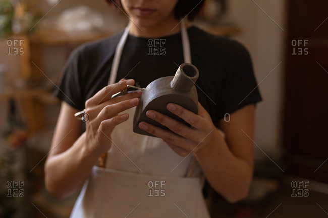 Front view mid section of a young Caucasian female potter holding a clay flask and a modelling tool in a pottery studio