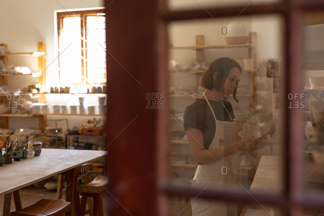 Side view of a young Caucasian female potter inspecting a dish in a pottery studio, seen through a glass door